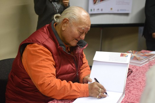 Rinpoche signing books. Photo by Paolo Fassoli