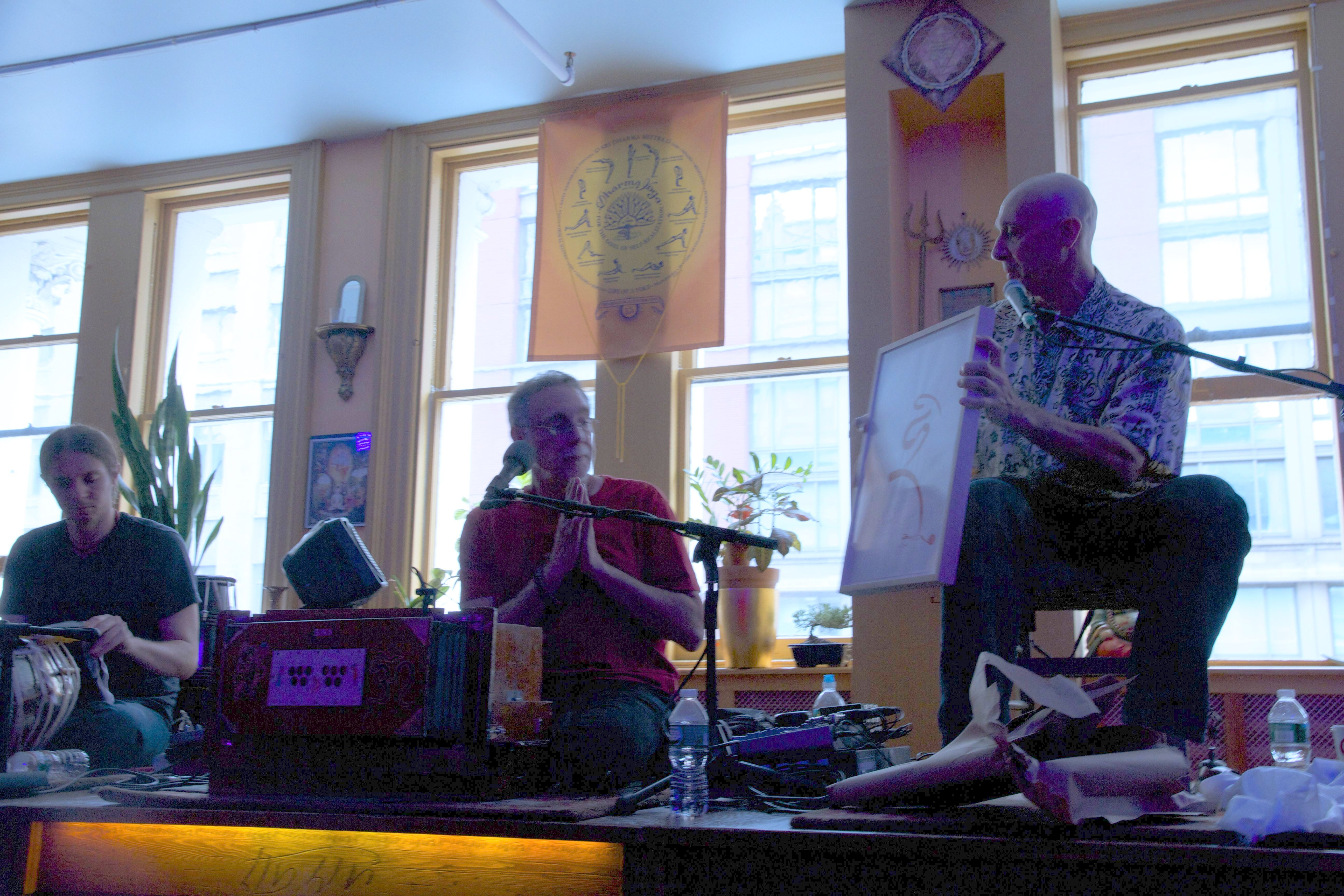 Michael Katz (right) presents a gift of calligraphy by Chögyal Namkhai Norbu to Krishna Das (center) at the Benefit Performance in NYC