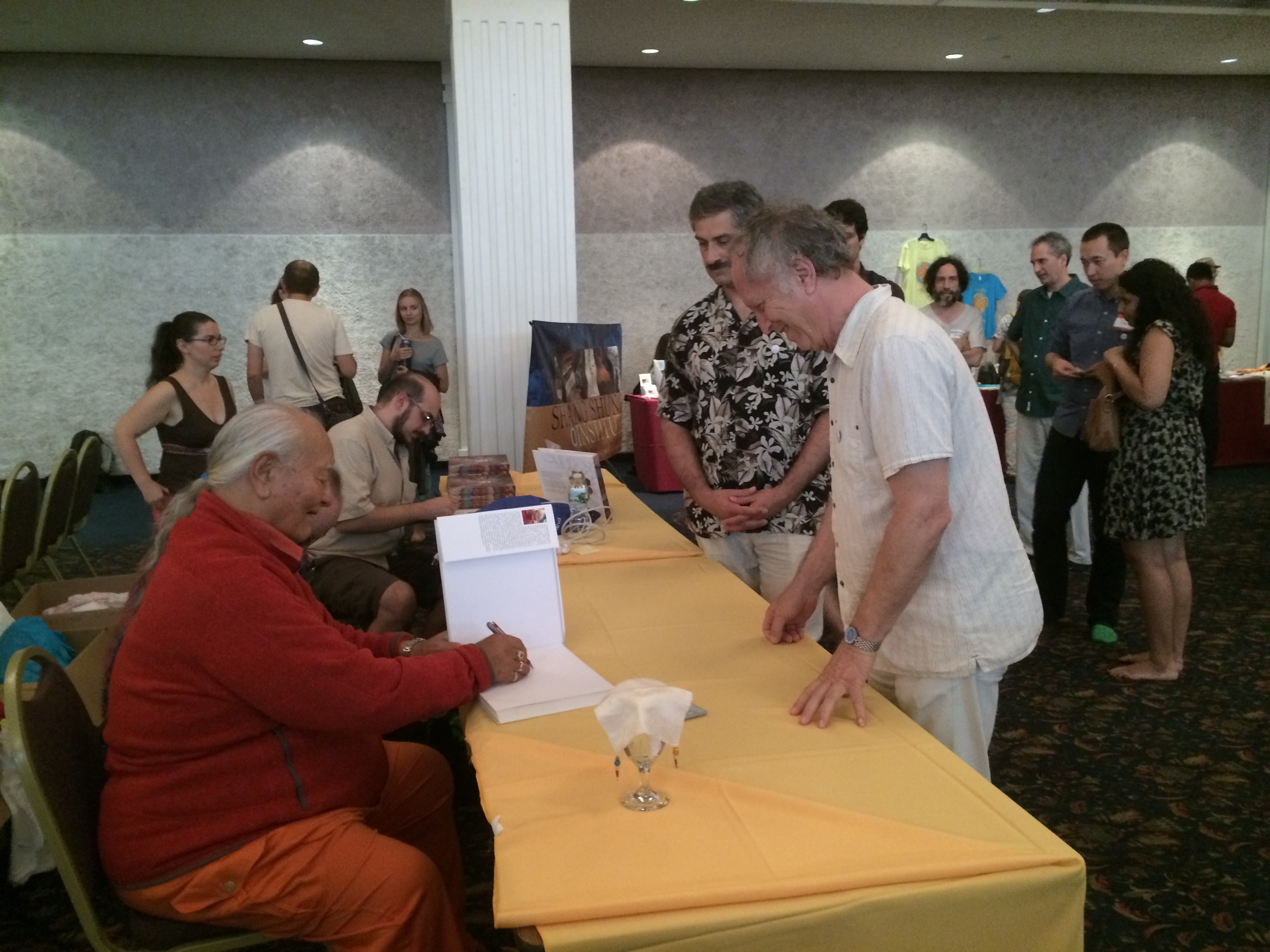 Rinpoche's signs the Merigar Gonpa book for people at the retreat