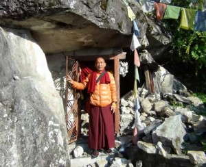 Khenpo Nyima Dondup standing outside the damaged Meditation Cave of the Self-Arisen Sun and Moon
